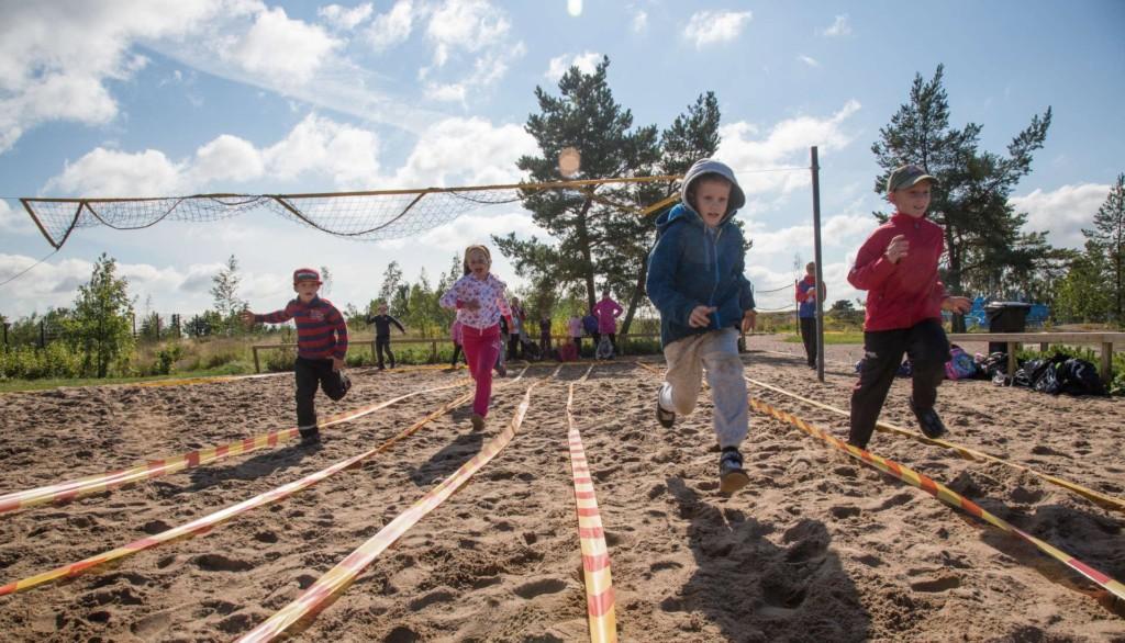 Lapset juoksevat beach volley kentalle rakennettuja juoksuratoja.