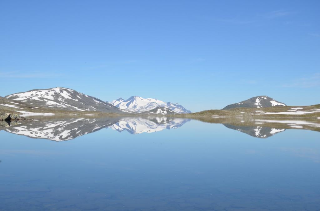 Tunturijärven pintaan heijastuu horisontin lumihuippuisia vuoria